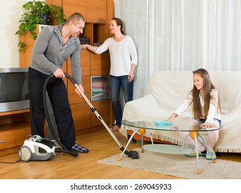 Little girl helping smiling parents to clean at home. Focus on man