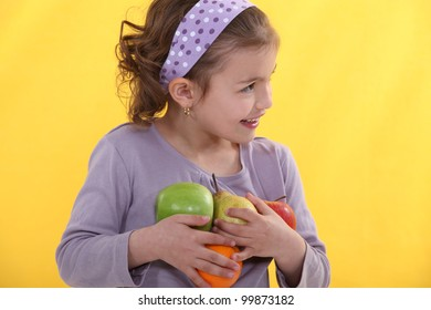 A little girl with her arms full of fruits.