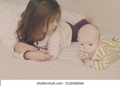 little girl and her baby brother on the bed