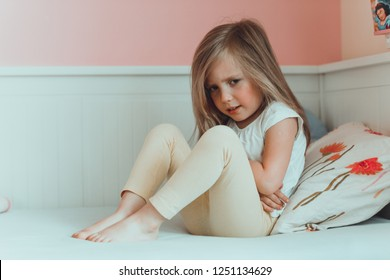 A little girl in her bed has a stomachache. Holding her hands on belly and suffering.