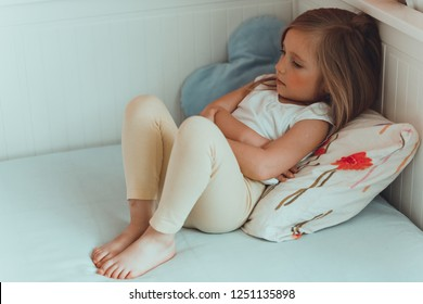 A little girl in her bed has a stomachache. Holding her hands on belly.