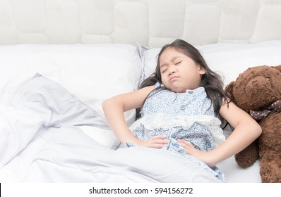 a little girl in her bed has a stomachache, healthy concept