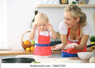 Little girl and her blonde mom in red aprons  playing and laughing while kneading the dough in the kitchen. Homemade pastry for bread, pizza or bake cookies