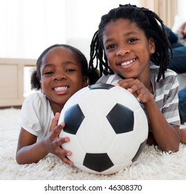Little girl and her brother holding soccer ball lying on the floor