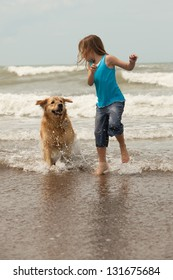 little girl and her dog running in the ocean