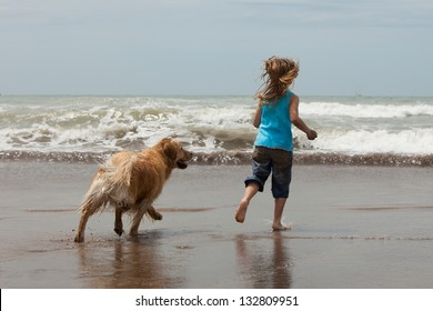 little girl and her dog running into the ocean