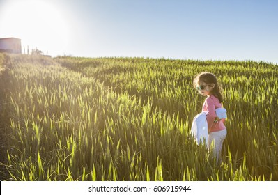 Little girl and her doll walking through green cereal field at sunset, Spain