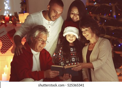 Little girl and her family reading book in living room decorated for Christmas