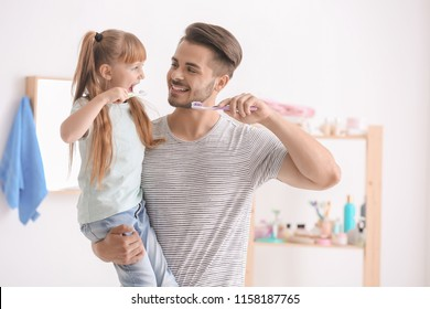 Little girl and her father brushing teeth in bathroom
