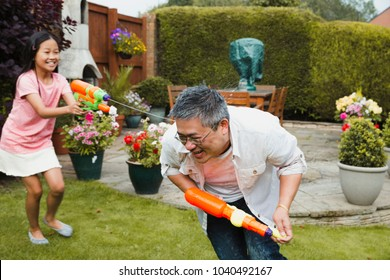 Little girl and her father are having a water fight in the garden with water pistols. The girl is getting the dad and he is crouching and trying to run away.