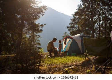 A little girl with her father near a tent in nature in a mountain fir forest. The father and daughter assemble a tent for outdoor recreation and are illuminated by the evening Golden light of the sun