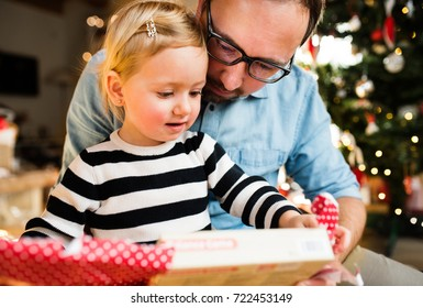 Little girl with her father opening Christmas present.