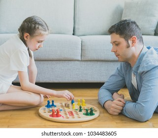 Little girl and her father playing ludo.