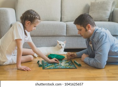 Little girl and her father playing board game.