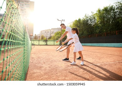 Little girl and her father playing tennis on court