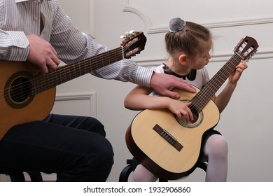little girl and her father are playing guitar. Learning to play the guitar. Music education and extra-curricular lessons.