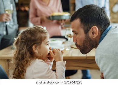 Little girl and her father sharing a spaghetti while eating at dining table.