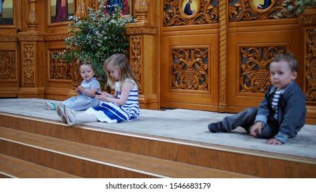 Little girl and her friends sitting on the step in the Orthodox Church., first visit and first impression in a Church.