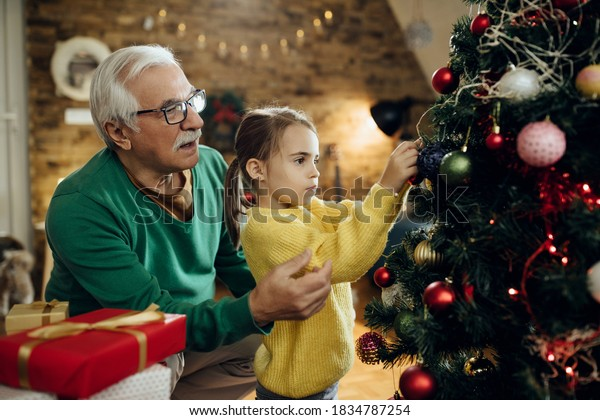Little girl and her grandfather decorating Christmas tree in the living room.