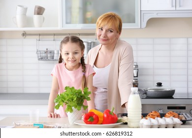 Little girl and her grandmother cooking in kitchen