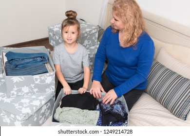 A little girl with her grandmother sorted out clothes and collected donations for people in need. Capsule wardrobe and order in the closet. Moving to a new house or apartment.