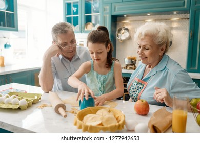 Little girl and her grandparents baking a pie and cookies together. Cooking with kids, family activity concept.