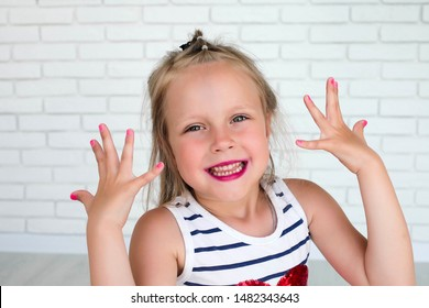 Little girl with her lips painted and shows her nails painted against a background with white bricks