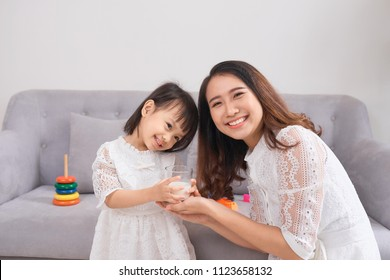 Little girl and her mom drinking milk sitting on sofa at home. Motherhood and care, healthy eating and lifestyle, early development concept, copy space