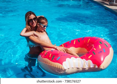 Little girl with her mom having fun in swimming pool.