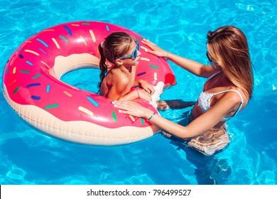 Little girl with her mom having fun in swimming pool.