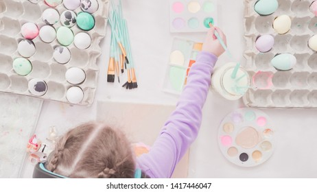 Little girl and her mom painting Easter art project with acrylic paint.