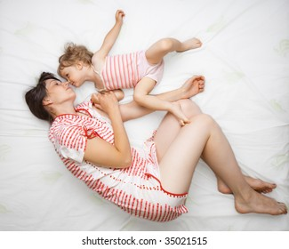 Little girl with her mom playing on a bed - view from above