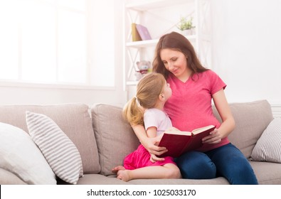 Little girl and her mom reading book sitting on the sofa at home. Mother and daughter study fairy tales. Motherhood, joint activities and interests, early development, caring concept, copy space