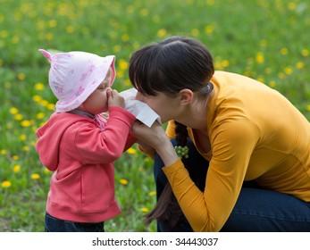 Little girl with her mom suffer from allergy - shallow DOF, focus on girl's eyes