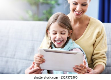 Little girl and her mom using tablet while sitting on sofa at home