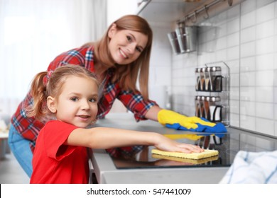 Little girl and her mother doing cleanup in kitchen