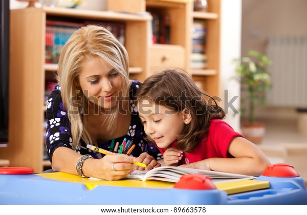 little girl and her mother drawing on a book at playtable