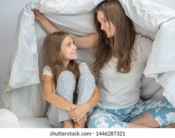 Little girl and her mother enjoy morning at home. Family playing under blanket on the bed in the bedroom