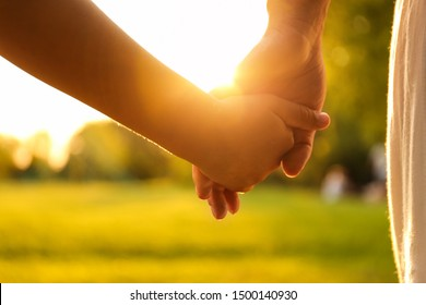 Little girl and her mother holding hands in park, closeup. Happy family