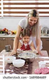 Little girl and her mother kneading dough with roller pin