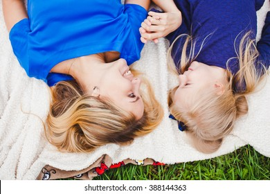 Little girl and her mother lying together on grass in summer. Family picnic. Beautiful young mom and her cute daughter blonds in blue dresses hold hands and look at each other. Overhead top view