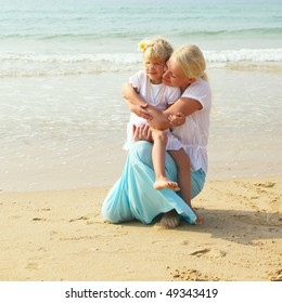 Little girl with her mother on the beach