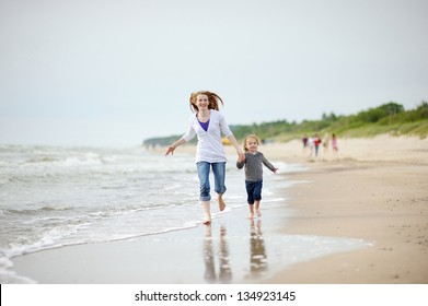 Little girl and her mother playing on the beach