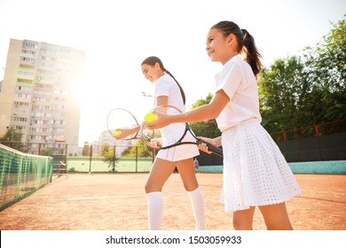 Little girl and her mother playing tennis on court