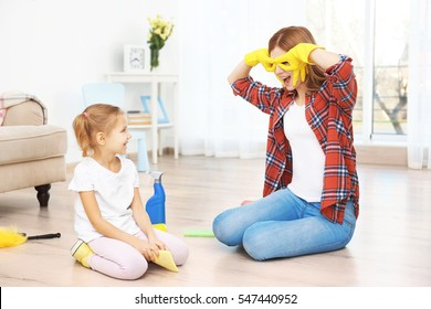 Little girl and her mother playing while doing cleanup at home
