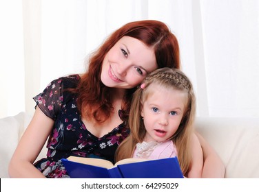The little girl and her mother read a book together on the couch