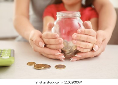 Little girl with her mother sitting at table and holding glass jar with coins, closeup. Money savings concept