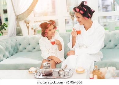 A little girl and her mother are sitting on couch. They have curlers on their heads. Mother and daughter in white bathrobes are holding cups of tea.