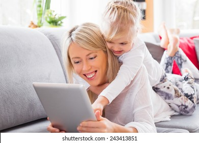 Little girl with her mother using tablet computer