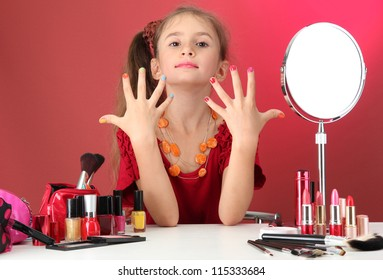 little girl in her mother's dress, is trying painting her nails